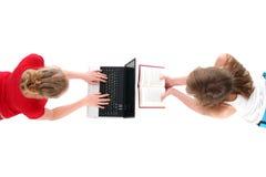Femmes utilisant l'ordinateur portatif et le livre de relevé Photos libres de droits
