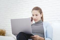 Femmes utilisant les chemises bleues qu'elle travaille et des conditions stressantes photographie stock