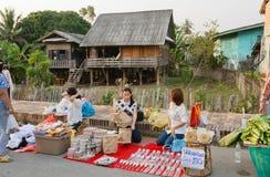 Femmes vendant des ustensiles de ménage à un marché en plein air le long des maisons en bois antiques Photographie stock libre de droits