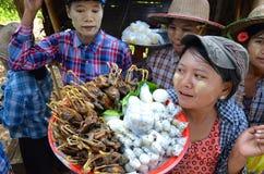 Femmes vendant toutes les marchandises là cuites le long de la route Image stock