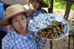 Femmes vendant toutes les marchandises là cuites le long de la route Photo stock