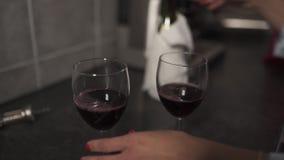 Femmes versant le vin rouge dans des verres étroitement - deux verres de vin vides banque de vidéos