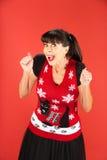 Femmina adulta emozionante in maglione brutto di Natale fotografia stock