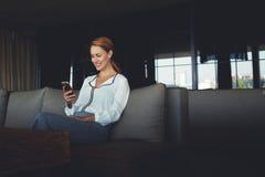 Femmina affascinante che ride mentre leggendo messaggio di testo sul telefono cellulare durante il resto in ristorante di lusso Fotografia Stock Libera da Diritti