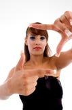 Femmina affascinante sorridente che mostra gesto d'inquadramento Immagini Stock