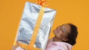 Femmina africana felice che tiene il contenitore di regalo importante in mani, pacchetto di festa, vendita stock footage