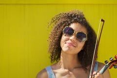 Femmina afroamericana con gli occhiali da sole che sorride alla macchina fotografica Immagini Stock