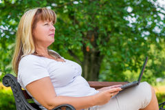 Femmina 50 anni, rilassantesi nel parco Immagini Stock