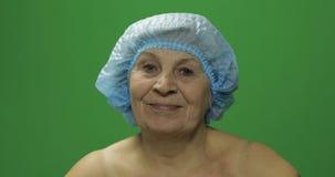 Femmina anziana sorridente in cappello protettivo che guarda alla macchina fotografica Chirurgia plastica immagine stock