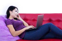 Femmina asiatica che chiama e che per mezzo del computer portatile - isolato Immagine Stock Libera da Diritti
