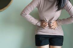 Femmina asiatica che ha mal di stomaco doloroso, donne che soffrono dal dolore addominale, dai crampi di periodo o dalla sindrome immagine stock libera da diritti