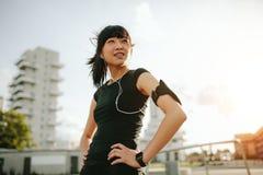 Femmina asiatica che prende una rottura durante il funzionamento di mattina immagine stock libera da diritti