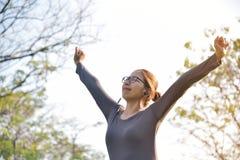 Femmina asiatica nell'allenamento grigio degli abiti sportivi al parco Immagine Stock