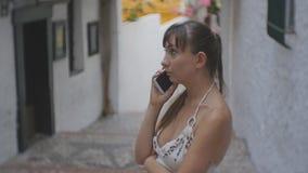 Femmina attraente che per mezzo dello smartphone Ritratto di giovane donna caucasica che parla su una via europea stretta con le  stock footage