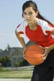 Femmina attraente che tiene una pallacanestro Fotografie Stock