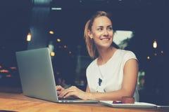 Femmina attraente con il bello sorriso che si siede con il NET-libro portatile in caffetteria Fotografia Stock Libera da Diritti