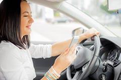 Femmina in automobile che esamina il suo Smart Phone Fotografia Stock