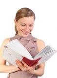 Femmina bionda che guarda il suo album di foto Immagini Stock