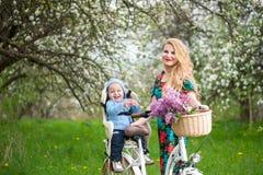 Femmina bionda con la bicicletta della città con il bambino nella sedia della bicicletta Fotografie Stock Libere da Diritti