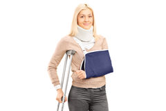 Femmina bionda felice con il braccio rotto che tiene una posa della gruccia Immagine Stock