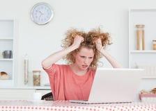 Femmina bionda Upset che si distende con il suo computer portatile Fotografia Stock