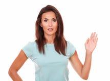 Femmina castana positiva con la mano di saluto Fotografie Stock