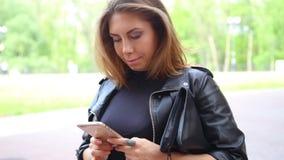 Femmina caucasica della donna adulta che per mezzo dello smartphone del cellulare di iphone sulla via video d archivio