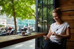 Femmina caucasica felice che guarda la sua foto sul telefono delle cellule mentre rilassandosi in caffè durante il tempo libero Fotografia Stock