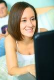 Femmina caucasica felice che si distende e che per mezzo del computer portatile Fotografia Stock