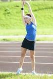 Femmina caucasica in Sportgear atletico che ha armi che allungano Excercises combinato con il piegamento del tronco Immagine Stock