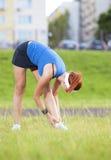 Femmina caucasica in Sportgear atletico che ha armi che allungano gli esercizi combinati con il piegamento del tronco Fotografia Stock