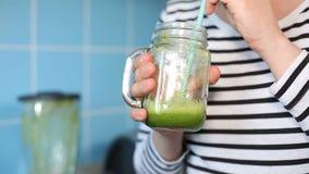 Femmina che assaggia un frullato verde video d archivio