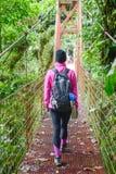 Femmina che attraversa un ponte sospeso Immagine Stock