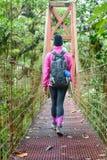 Femmina che attraversa un ponte sospeso Fotografia Stock Libera da Diritti