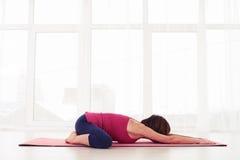 Femmina che fa allungando esercizio sulla stuoia di yoga Fotografia Stock