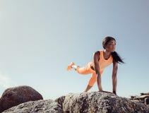 Femmina che fa allungando gli esercizi sulle rocce della spiaggia Immagine Stock Libera da Diritti