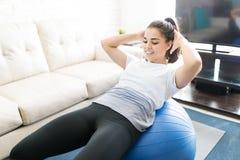 Femmina che fa gli scricchiolii dell'ABS sulla palla dei pilates Fotografie Stock