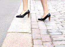 Femmina che fa un passo sul marciapiede Immagine Stock Libera da Diritti