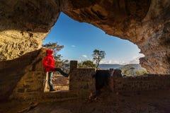 Femmina che guarda fuori dalle montagne blu Australia della caverna Fotografia Stock Libera da Diritti