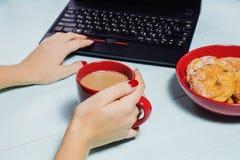Femmina che per mezzo del computer portatile con una tazza di caffè sulla tavola di legno Immagine Stock Libera da Diritti