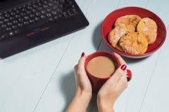 Femmina che per mezzo del computer portatile con una tazza di caffè sulla tavola di legno Fotografia Stock