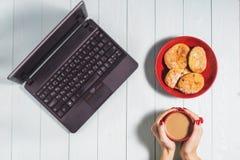 Femmina che per mezzo del computer portatile con una tazza di caffè sulla tavola di legno Fotografia Stock Libera da Diritti