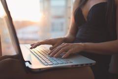 Femmina che per mezzo delle mani del ` s della donna del computer portatile a casa sul computer portatile Immagini Stock Libere da Diritti