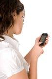 Femmina che per mezzo di un telefono moderno delle cellule Immagine Stock