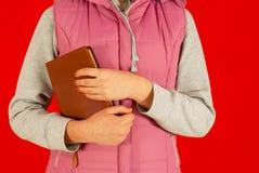 Femmina che rimane con un libro Fotografia Stock