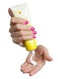 Femmina che si applica crema alle sue mani Fotografie Stock Libere da Diritti