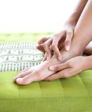 Femmina che si dà massaggio del piede Fotografie Stock