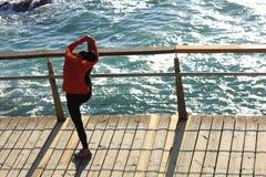 femmina che si scalda allungando le gambe sul sentiero costiero della spiaggia Immagine Stock Libera da Diritti