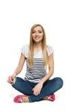 Femmina che si siede con le gambe attraversate sul pavimento Immagini Stock