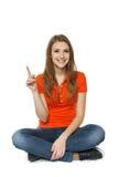 Femmina che si siede sul pavimento, indicante su Fotografia Stock Libera da Diritti